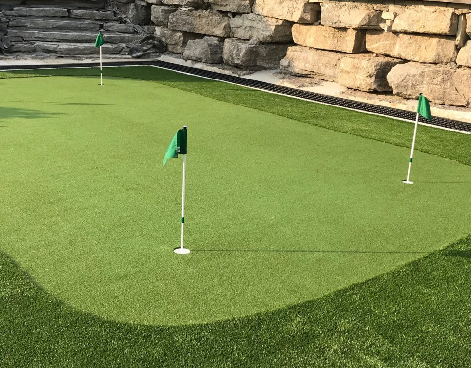 Stunning golf green and fringe turf with large Armour stone wall